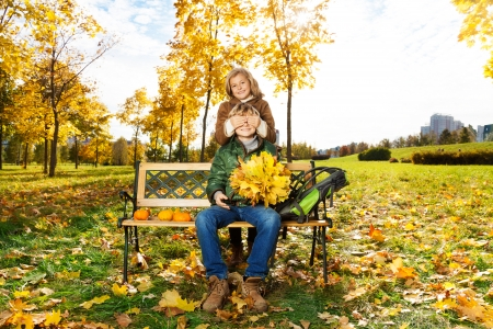 Little blond girl hide boys eye with guess who surprise in autumn park photo