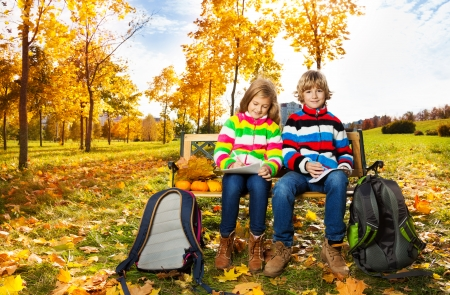 Portrait of two happy blond kids, twins brother and sister sitting on the bench after school  photo