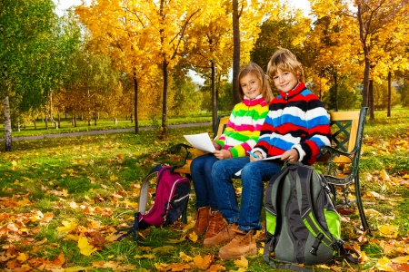 Portrait of two happy blond kids, twins sitting on the bench after school drawing pictures on paper photo