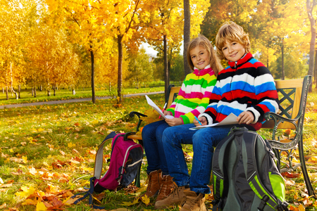 Portrait of two happy blond kids, twins sitting on the bench after school drawing pictures on paper with backpacks  photo