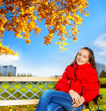 Autumn portrait of a 11 years old girl sitting on the bench in the park Stock Photo