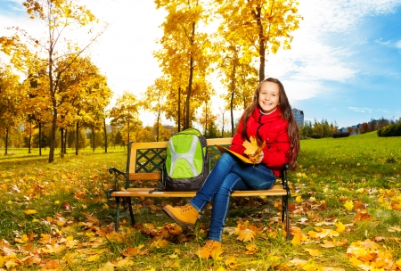 eleven: Autumn portrait of a 11 years old girl sitting on the bench in the park after school with backpack Stock Photo
