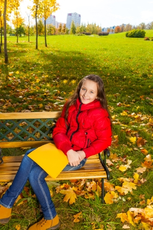 11: Autumn portrait of a 11 years old girl sitting on the bench in the park after school with paper folder Stock Photo
