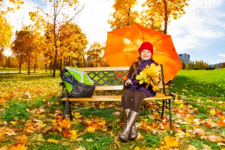 Cute little 6 years old girl holding maple leaves bouquet sitting on the bench with backpack after school in autumn park  photo