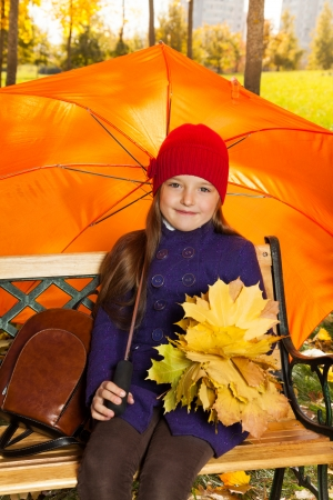 Cute little 6 years old girl holding maple leaves bouquet sitting on the bench with backpack after school in autumn park under umbrella  photo