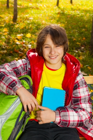Close portrait of 12 years old boy after school smiling and sitting in park photo