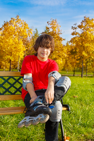 twelve month old: Happy 12 years old boy in red shirt sitting on bench and putting on skates in the autumn park