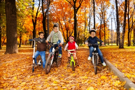Group of black boys and girl, brothers and sister riding bikes in the autumn October park with maple leaves photo