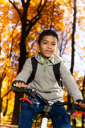 10 month: Close portrait 10 years old black boy riding a bicycle in the autumn park