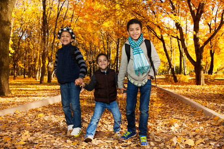 Three happy, laughing black boys, happy brothers 5-10 years old going together holding hands in the park wearing backpacks and autumn clothes in maple park photo