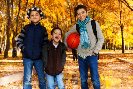8 10 years: Three black boys, brother 5 8 10 years old standing with basketball ball in autumn park with orange maple trees smiling and laughing