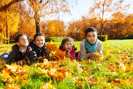 lying in leaves: Group of four black boys and girl, happy brothers and sister 3-10 years old laying in grass together  in the park in autumn clothes holding maple leaves bouquets
