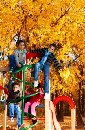 Four black boys and girl sitting on climbing frame together in autumn park playground photo