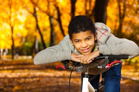10 month: Happy and smiling nice black 10 years old boy laying on the bicycle stern