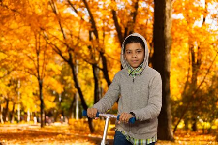 10 month: Close portrait handsome black 10 years old boy riding a scooter in autumn park with maple orange leaves and wearing hood