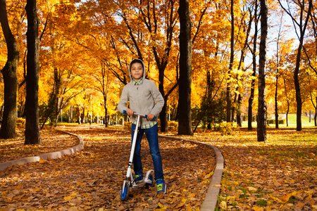 One handsome black 10 years old boy riding a scooter in autumn park with maple orange leaves wearing autumn sweatshirt with hood photo