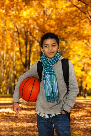 Handsome black boy 10 years old standing in the autumn park under maple trees with orange basketball ball photo