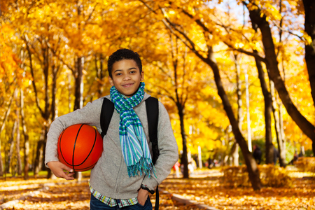 kids playing sports: Handsome black boy 10 years old standing in the autumn park under maple trees with orange basketball ball wearing casual clothes with scarf and sweatshirt