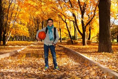 10 month: Handsome smiling black boy 10 years old standing in the autumn park under maple trees with orange basketball ball wearing casual clothes with scarf and sweatshirt Stock Photo