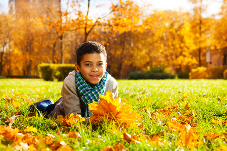 10 month: Nice 10 years old black smiling boy laying in grass filled with autumn leaves