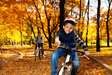 1 2 month: Happy smiling 8 years old black boy riding a bike in the autumn park with his older brother