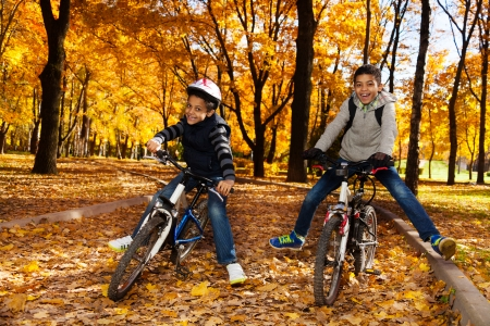 Two black 8 and 10 years old boys ride a bikes in the autumn maple and oak tree park