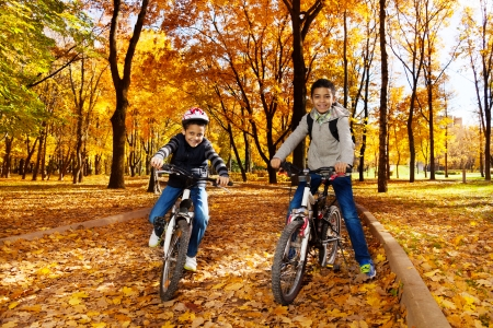 8 10 years: Two black 8 and 10 years old boys ride bicycles, wearing helmet in the autumn maple and oak tree park Stock Photo