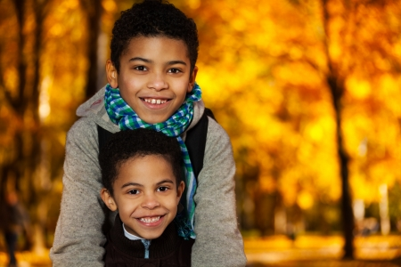 kids hugging: Close portrait of two happy 8 and 10 boys black brothers standing in the autumn orange park Stock Photo