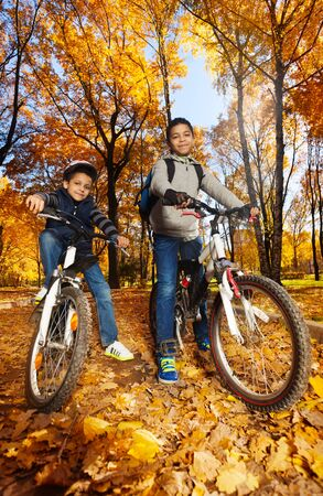 1 2 month: Two cute black smiling 8 and 10 years old boys ride bicycles, wearing helmet in the autumn maple and oak tree park