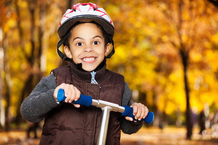 Close portrait of happy smiling 5 years old black boy wearing helmet riding scooter in the autumn photo