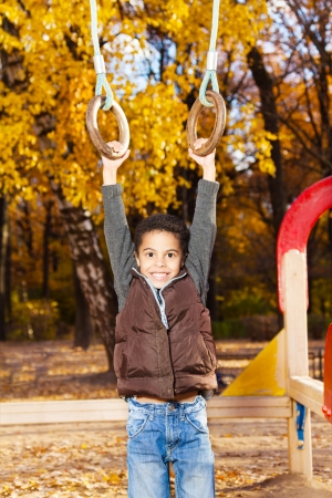 5 years: 5 years old black boy hanging in on rings on playground in the autumn park