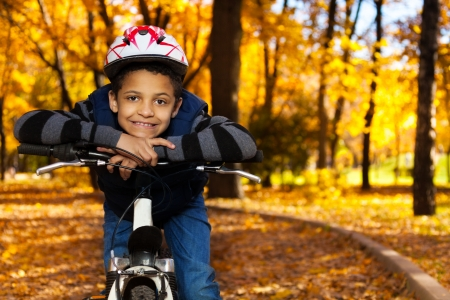Close portrait of happy smiling 8 years old black boy riding a bike in the autumn park leaning on bicycle stern photo