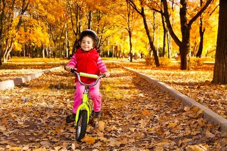 fille noire: Petite fille noire une bicyclette dans le parc sur la route couverte de ch�ne d'automne et d'�rables