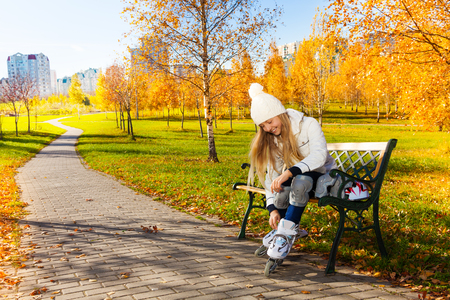 Blond teen girl with long hair in autumn park sitting on the bench and putting on roller blades photo