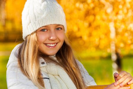 Close portrait of blond teen girl with long hair and happy toothy smile with autumn background