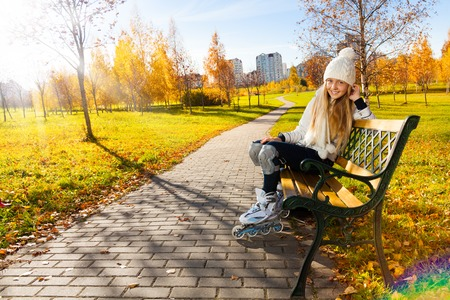 Happy blond teen girl with long hair in white warm clothes sitting on the bench wearing roller skates photo