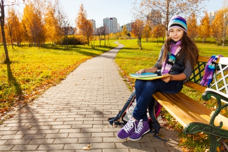 11 years: Cute 11 years old girl in warm clothes in the park sitting on the bench in autumn park Stock Photo