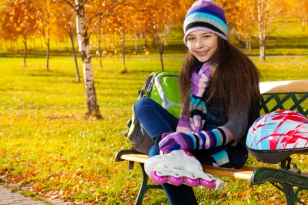 11 years: Close portrait of beautiful 11 years old girl putting on roller blades in warm clothes in the park sitting on the bench in autumn park with helmet laying on the bench