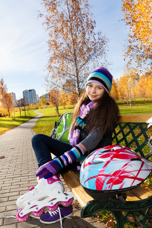 11 years: Cute 11 years old girl putting on roller blades in warm clothes in the park sitting on the bench in autumn park with helmet laying on the bench