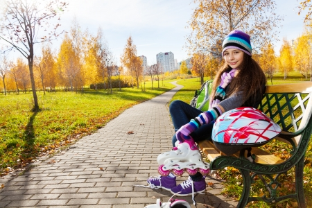 11: 11 years old beautiful girl sitting on the bench in the park putting on roller blades to go skating in the autumn park on sunny day Stock Photo