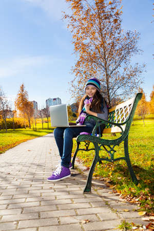 11 years: Beautiful school girl 11 years old sitting on the bench in park with laptop top on sunny autumn day