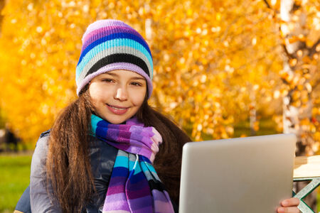 11 years: Girl with tablet computer 11 years old sitting in the park on sunny autumn day Stock Photo