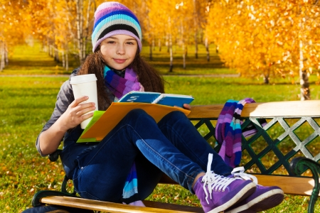 11 years old: Portrait of nice smiling 11 years old girl holding coffee mug and textbook wearing blue purple hat and scurf