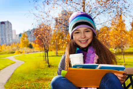 11 years: Close portrait of nice happy smiling 11 years old girl holding coffee mug and textbook wearing blue purple hat and scurf sitting on the bench in the park