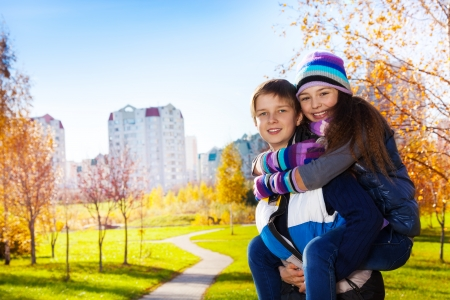 10 and 11 years old couple of school kids, boy an girl in warm autumn clothes photo