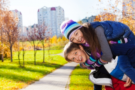 10 11 years: Boy carry girl, both happy and laughing 10 and 11 years old couple of school kids, in warm autumn clothes Stock Photo