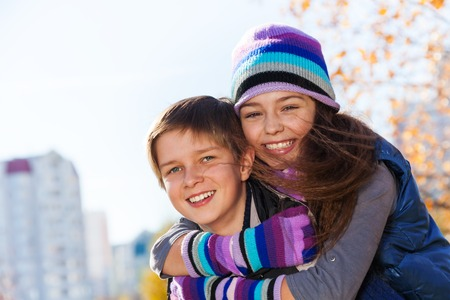 10 11 years: Boy and girl hugging and smiling 10 and 11 years old wearing warm autumn clothes outside