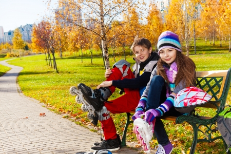 10 11 years: Children putting on roller blades 10 and 11 years old couple of school kids, boy an girl in warm autumn clothes on the bench in park Stock Photo