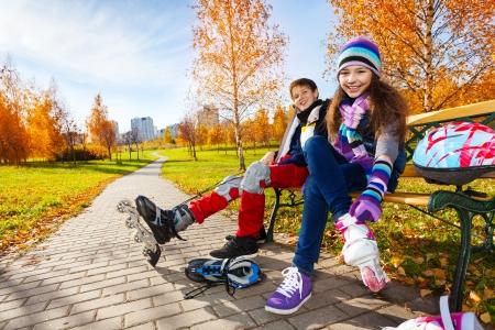 niño en patines: 10 y 11 años de edad par de niños de la escuela, muchacho una muchacha que pone en patines en ropa de otoño caliente