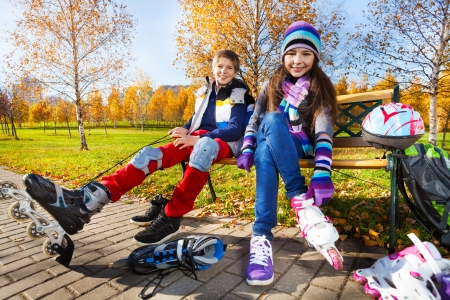 rollerblading: 10 and 11 years old couple of school kids, boy an girl putting on roller blades in warm autumn clothes in the park shoot from low angle